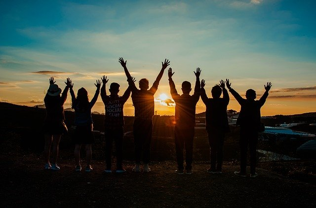Picture of young people in front of a sunset